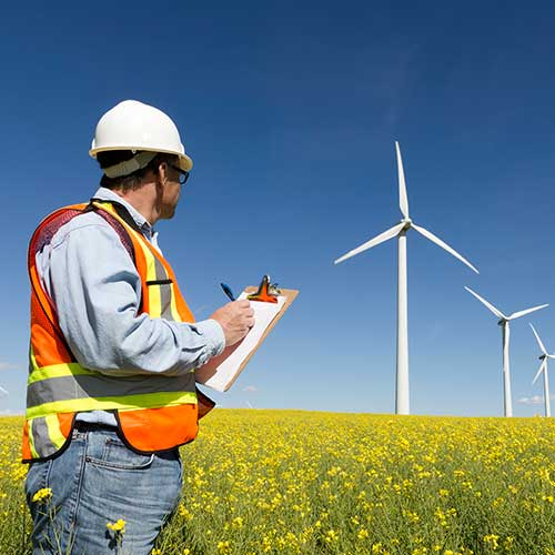 Power company worker inspecting windmills